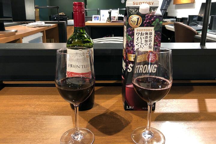グラスにワインを注いで比べている